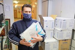 Zdjęcie przedstawia pracownika jednostki pomocy i integracji społecznej z kombinezonami ochronnymi.