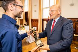 Lekkoatleta Rafał Kot odbiera statuetkę Juranda z rąk Jarosława Matłacha Starosty Szczycieńskiego